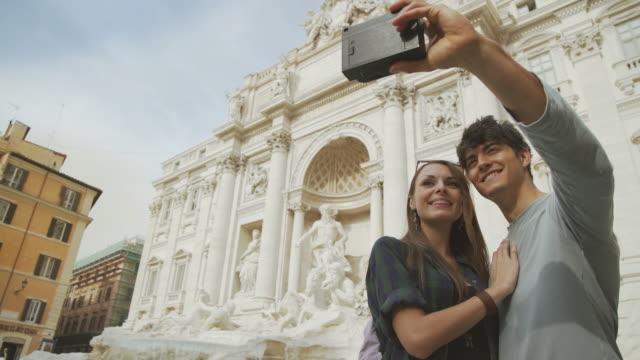 stockvideo's en b-roll-footage met toeristische paar nemen een selfie met vintage instant camera - polaroid