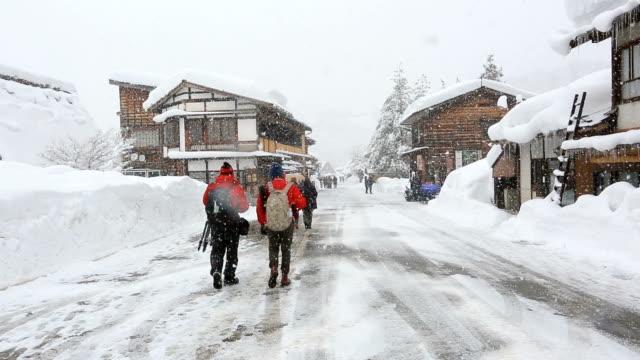 Tourist crowd in Shirakawago world heritage Japan with snowfall video