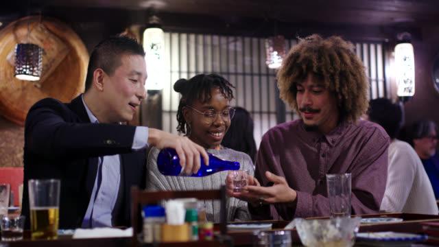 日本の伝統的な居酒屋での地元の人々との観光酒 - アフリカ民族点の映像素材/bロール
