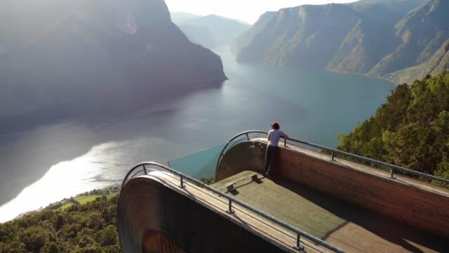 tourist enjoying fjord view on stegastein viewpoint norway - fiordo video stock e b–roll