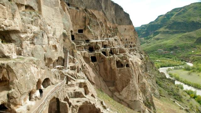 stockvideo's en b-roll-footage met een toerist onderzoekt de bezienswaardigheden van georgia vardzia grot klooster - klooster