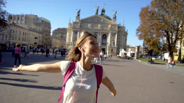 stockvideo's en b-roll-footage met toeristische meisje met plezier en genieten van vrijheid - wit t shirt