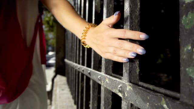 stockvideo's en b-roll-footage met toeristische meisje uitgevoerd en aanraken van hek - wit t shirt