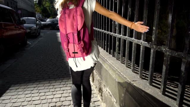 stockvideo's en b-roll-footage met toeristische meisje rennen de stoep - wit t shirt