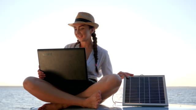 tourist girl sits on car roof in backlight holds in hands laptop charging solar array, young woman sitting on vintage car video