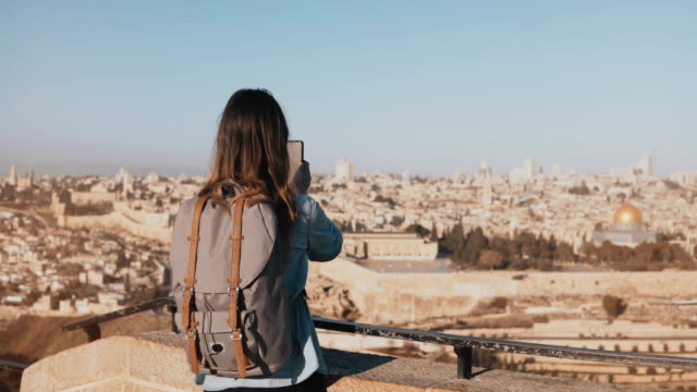 Tourist girl takes photos of old town Jerusalem. Girl with backpack walks to skydeck edge. Capturing moments. Israel 4K video