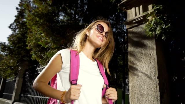 stockvideo's en b-roll-footage met toeristische meisje wandelen langs de stoep - wit t shirt