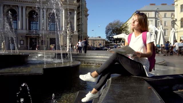 stockvideo's en b-roll-footage met toeristische meisje kijken kaart in fontein - wit t shirt