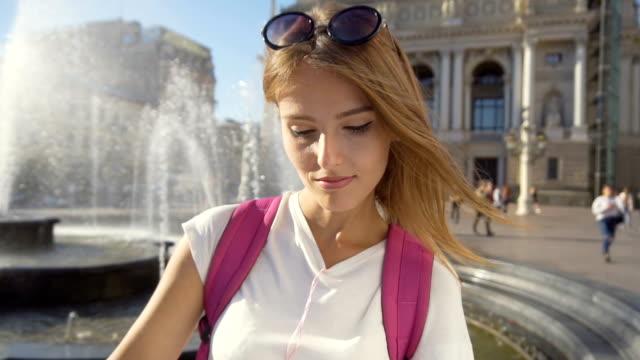 stockvideo's en b-roll-footage met toeristische meisje kijken kaart in de buurt van fontein - wit t shirt