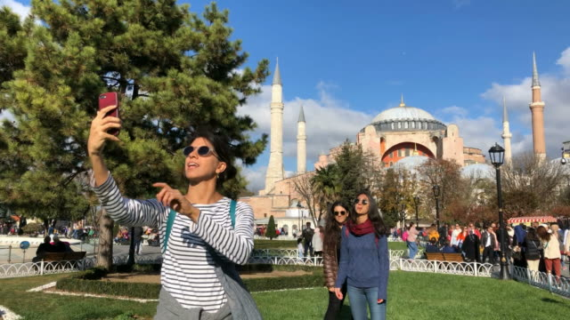 vídeos de stock e filmes b-roll de tourist girls making selfies in sultanahmet square, istanbul - istambul