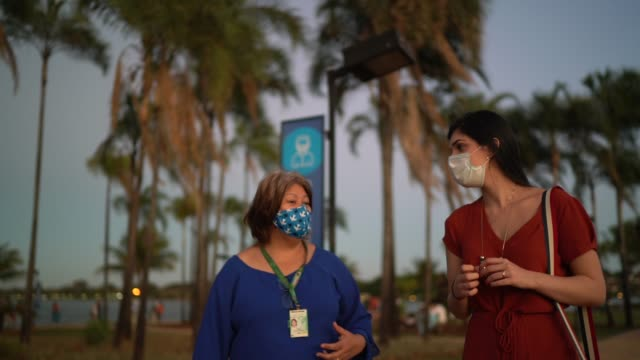 Tourist guide and young traveller woman showing and visit sidewalk - wearing face mask