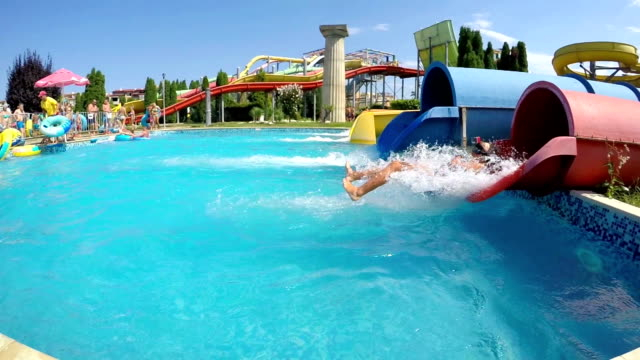 SUNNY BEACH, BULGARIA - 29 JULY, 2016: Tourist has into pool after going down water slide, SLOW MOTION SUNNY BEACH, BULGARIA - 29 JULY, 2016: Tourist has into pool after going down water slide, SLOW MOTION aquatic organism stock videos & royalty-free footage