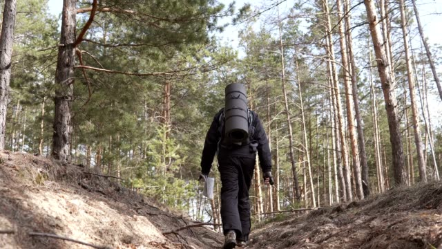 A tourist in a forest area goes on a map to a place of deployment - vídeo