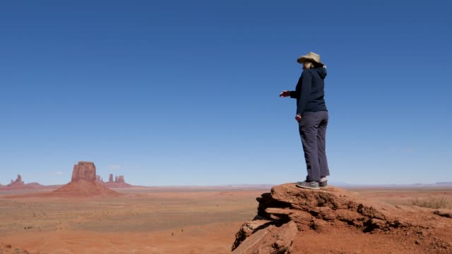 Tourist In Cowboy Hat Walking To Cliff Edge Of Viewpoint In Monument Valley Usa