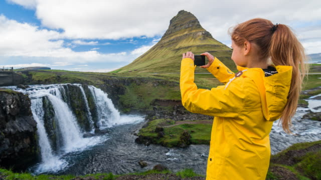 Tourist in Iceland taking pictures of Kirkjufellsfoss waterfall video