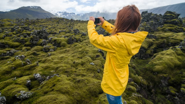 Tourist in yellow raincoat photographing moss cover on volcanic landscape of Iceland