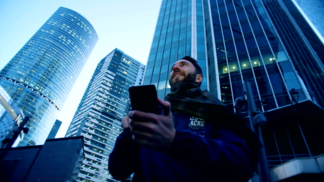tourist is operating his smartphone while being next to skyscrapers. epic cinema camera shot. - azionare video stock e b–roll