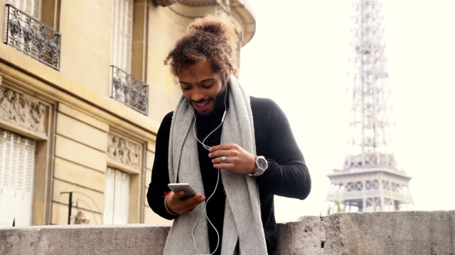 Half African tourist listening to new songs in earphones with smartphone near Eiffel tower video