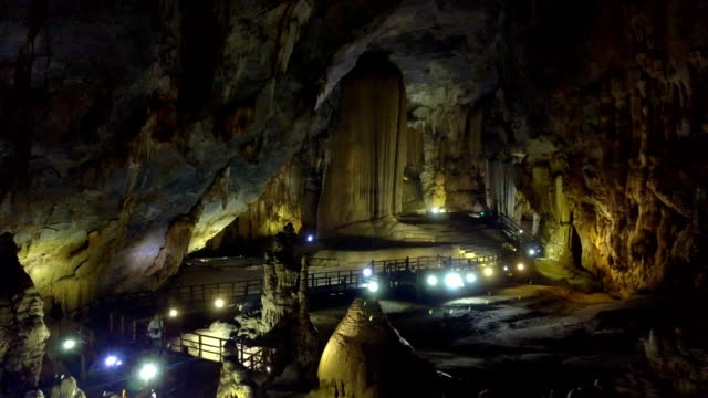 tourist looks at magical structures of karst cave hall
