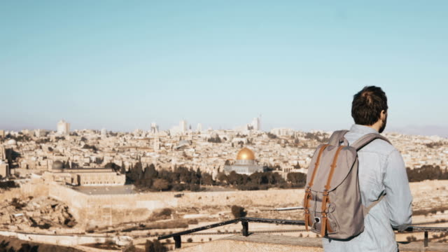 Tourist male takes photos of Jerusalem panorama. Man with backpack stands at skydeck edge with smartphone. Israel 4K video