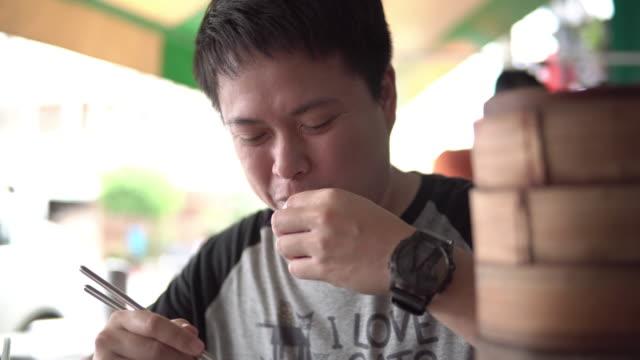 tourist mann essen dim sum (chinesische küche) im restaurant. - kloß stock-videos und b-roll-filmmaterial