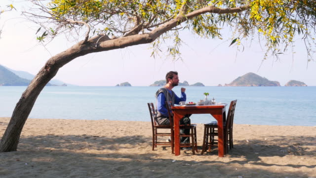 Tourist man eating gorgeous breakfast beach with majestic sea background video