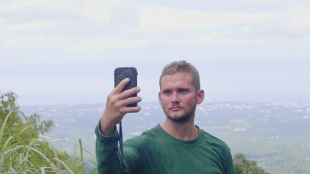 vidéos et rushes de homme de touriste faisant la photo de selfie par le téléphone mobile sur la vue panoramique du sommet de montagne. blogueur de voyage posant pour selfie mobile sur le paysage de vallée de montagne du sommet élevé. - photophone