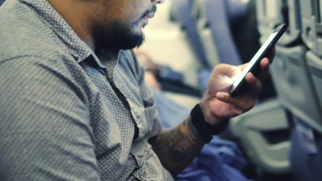 좌석에 앉아서 비행 중 휴대 전화를 사용 하 여 남자를 관광. - airplane seat 스톡 비디오 및 b-롤 화면