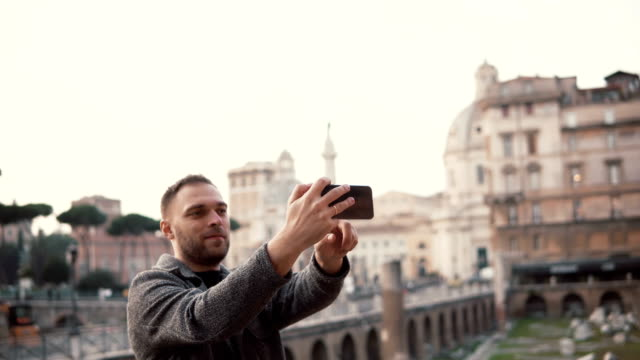 Tourist man takes selfie photos against the background of city centre of Rome, Italy with his smartphone, smiling video