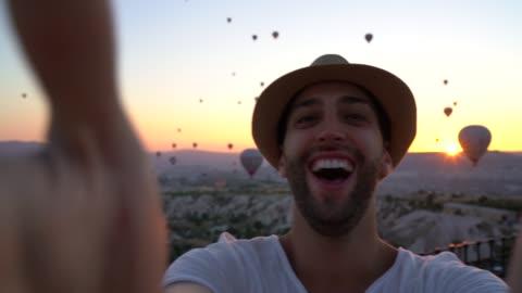 vídeos y material grabado en eventos de stock de hombre turista tomando un selfie en capadocia, turquía - turismo vacaciones