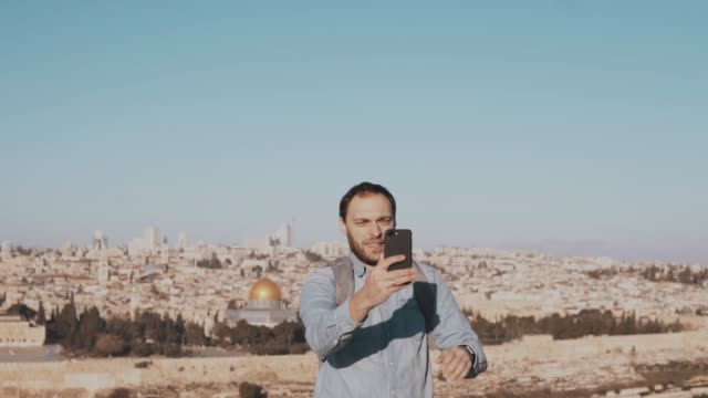 Tourist man talks on phone video call. Jerusalem, Israel. European male traveler chats happy and excited. Slow motion video