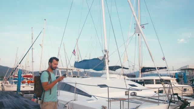 vídeos de stock, filmes e b-roll de homem do turista com a trouxa usando seu smartphone no cais do porto com iate do catamarã no fundo - marina