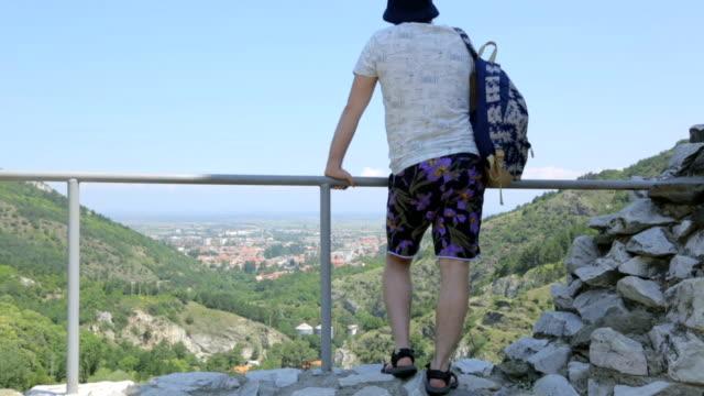 vídeos de stock e filmes b-roll de tourist on mountain looking down - man admires forest