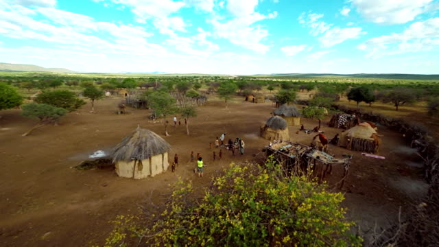 HELI Tourist Photographing The Himba Tribe HD1080p: AERIAL HELI shot of a tourist photographing in the Himba village. Northern Namibia, Namibia. Africa. minority groups stock videos & royalty-free footage