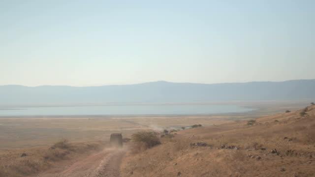 航空写真: 観光サファリ ジープ gamedrive ンゴロンゴロ火山火口にスピード違反で - 乾燥点の映像素材/bロール
