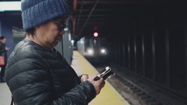 Tourist senior woman waiting and texting with cell phones on subway platform Asian senior woman traveler using smartphone and waiting a train in the station at New York City. USA railroad station platform stock videos & royalty-free footage