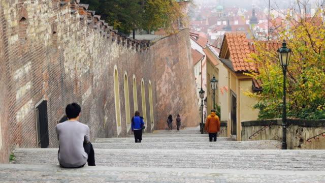 Tourist sitting at ladder old town prague video
