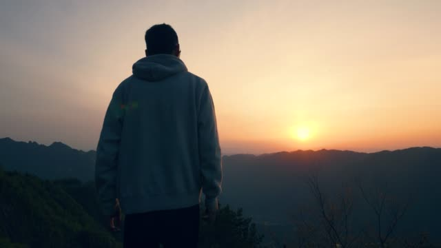 Tourist standing on top of mountain looking sunset
