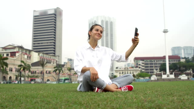 Tourist take photos and selfies on grass in Kuala Lumpur video