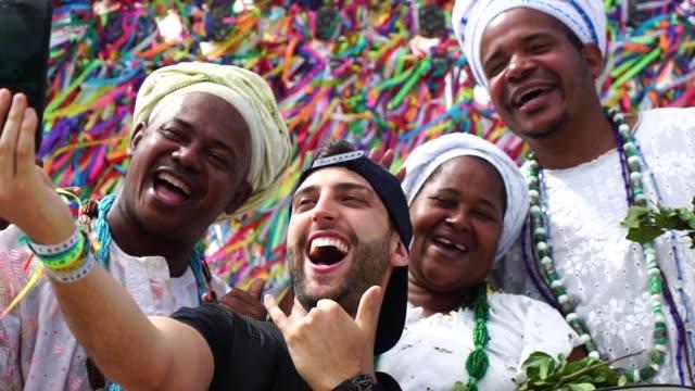 vídeos de stock, filmes e b-roll de turísticos, levando um selfie com grupo de candomblé, na igreja do bonfim, em salvador, bahia, brasil - nordeste