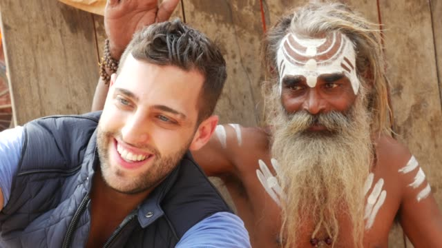 vídeos de stock e filmes b-roll de tourist taking a selfie with sadhu - holy man, in varanasi, india - hinduísmo