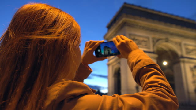 Tourist taking pictures of Arc de Triomphe with phone at night video