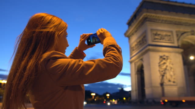 Tourist taking pictures of Arc de Triomphe with smartphone at night video