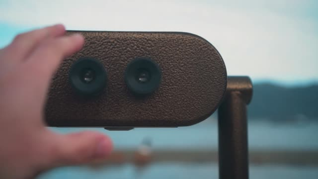 Tourist telescope Panorama Binoculars, side view. A metal coin works with a gray telescope, isolated on a view of a landscape, blue sky, sea water and mountains. The male hand touches the binoculars