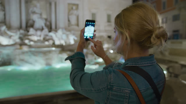 SLO MO Tourist using her smartphone to take pictures of the Trevi Fountain at night Slow motion shot of a female tourist using her smartphone to take pictures of a famous Trevi Fountain at night. Rome. Italy. Shoot in 6K resolution. renaissance architecture stock videos & royalty-free footage