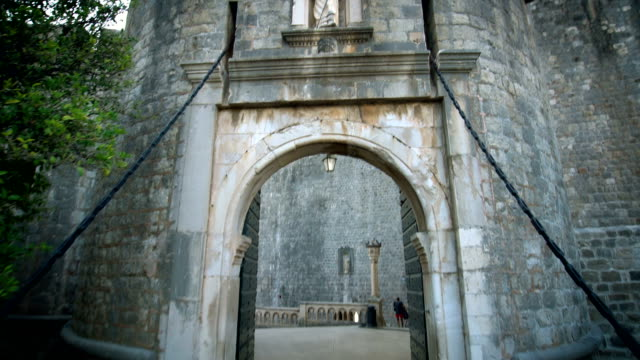 vídeos de stock, filmes e b-roll de pov turista caminhar através da porta de entrada de dubrovnik. - castelo