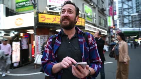 vidéos et rushes de touriste marchant par des rues de tokyo utilisant l'application - tourisme