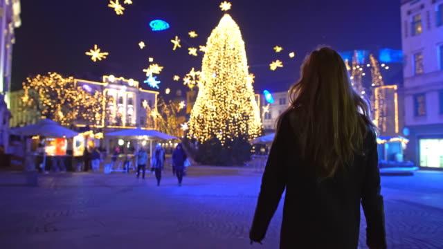 touristen, die zu fuß in richtung weihnachtsbaum am stadtplatz - weihnachtsmarkt stock-videos und b-roll-filmmaterial