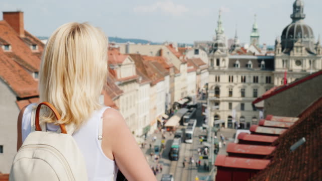 A tourist with a backpack behind him admires the beautiful view of the old European city of Graz. Euro-trip video