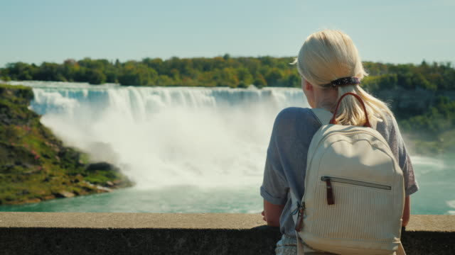 a tourist with a backpack behind him looks at niagara falls. rear view, taken from the canadian coast. in the picture you can see a waterfall on the american shore - niagara falls stock videos & royalty-free footage